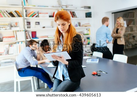 Businesswoman in modern office working with tablet in hand - stock photo