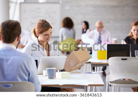 Businesswoman In Office Booking Courier Collection - stock photo