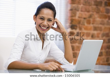 Businesswoman in office with laptop laughing - stock photo