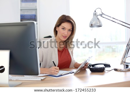 Businesswoman in office working with tablet - stock photo