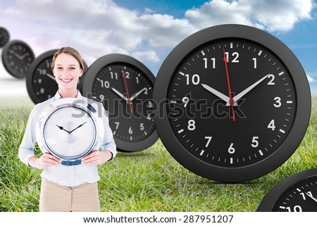 Businesswoman in suit holding a clock against sunny landscape - stock photo