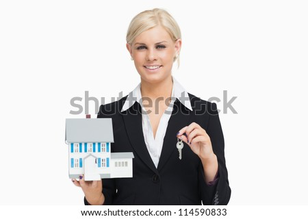 Businesswoman in suit holding a model house against white background - stock photo