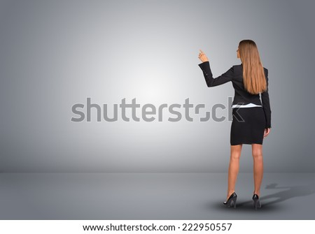 Businesswoman in suit standing in an empty gray room and pointing finger at wall. Rear view - stock photo