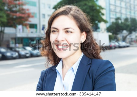 Businesswoman in the city looking sideways - stock photo