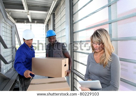 Businesswoman in warehouse controlling goods reception - stock photo