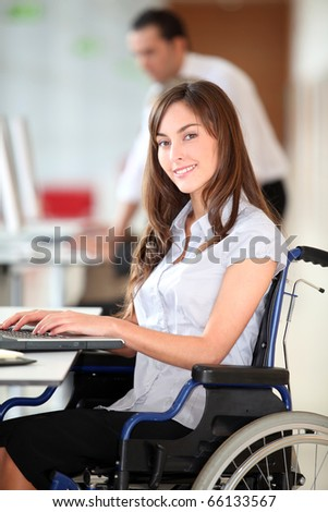 Businesswoman in wheelchair working in the office - stock photo