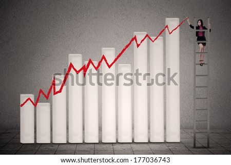 Businesswoman is climbing ladder while drawing profit chart - stock photo