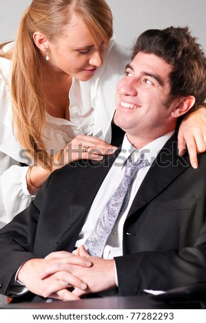 businesswoman is embracing her teammate trying to flirt with him - stock photo