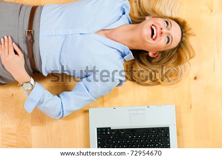 Businesswoman is lying on the floor at home relaxing, a laptop beside her - stock photo