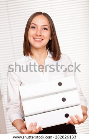 Businesswoman is standing with folders over white isolated background - stock photo