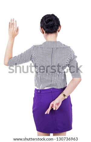 Businesswoman is standing with her fingers crossed behind her back - stock photo