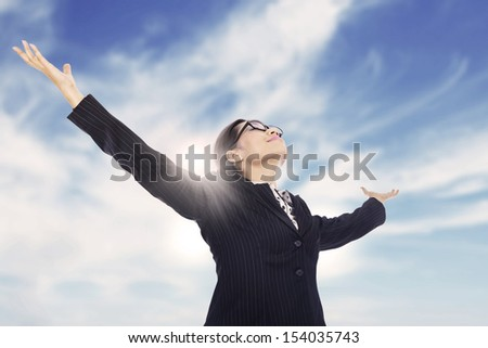 Businesswoman is stretching her arms under the blue sky - stock photo