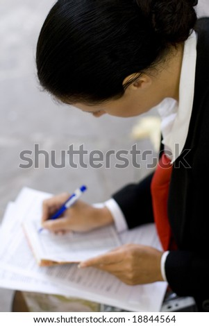 businesswoman is writing notes and planning her schedule. - stock photo