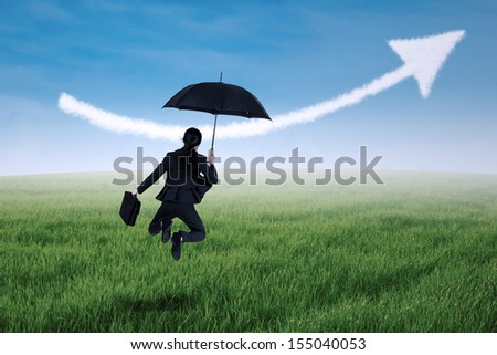 Businesswoman jumping holding umbrella in meadow and arrow up sign - stock photo