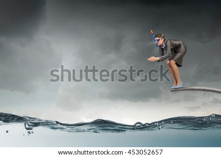 Businesswoman jumping in water . Mixed media - stock photo