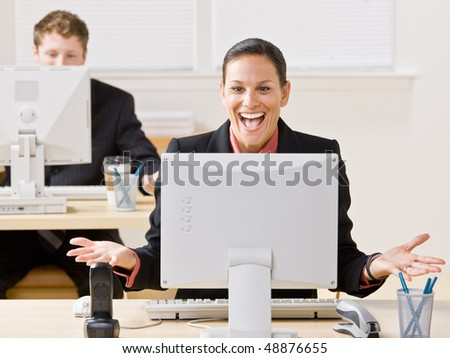 Businesswoman laughing at monitor - stock photo