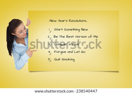 Businesswoman looking around the corner while pointing against yellow card - stock photo