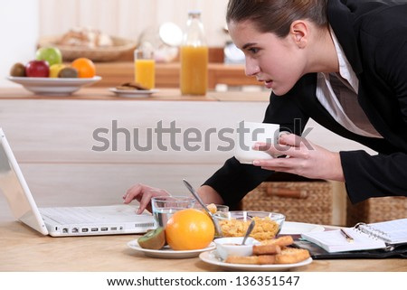 Businesswoman looking at a laptop over breakfast - stock photo