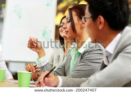 Businesswoman looking at business card in meeting - stock photo