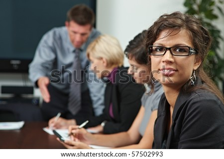 Businesswoman looking at camera during business training, smiling. - stock photo