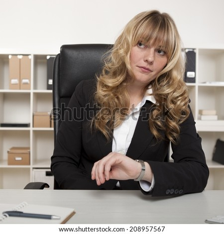 Businesswoman looking at her watch as she sits at her desk, waiting for a meeting indicating that someone is late or a deadline is near. - stock photo