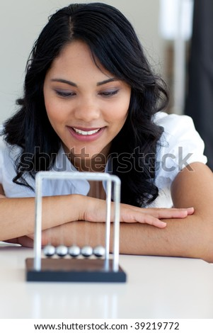Businesswoman looking at kinetic balls in office - stock photo
