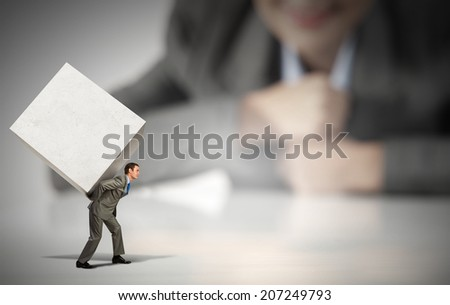 Businesswoman looking at miniature of man carrying white cube on back - stock photo