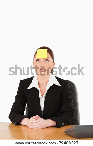 Businesswoman looking at the sign on her forehead against a white background - stock photo