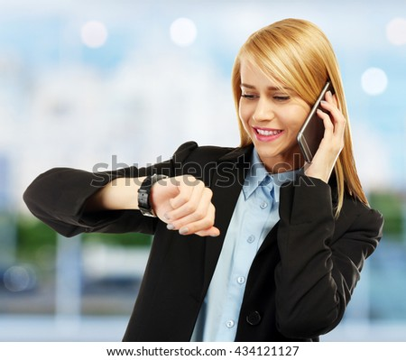 Businesswoman looking at wrist watch on blurred background - stock photo