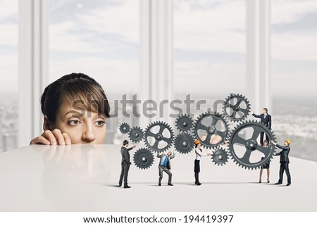 Businesswoman looking from under the table at businessteam - stock photo