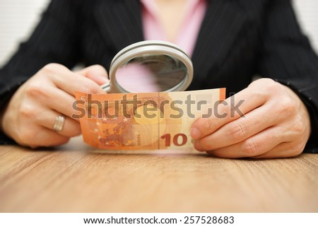 Businesswoman looking through a magnifying glass money. fraud concept - stock photo