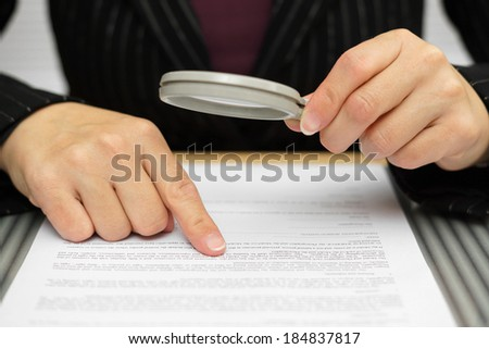 Businesswoman looking through a magnifying glass to contract - stock photo