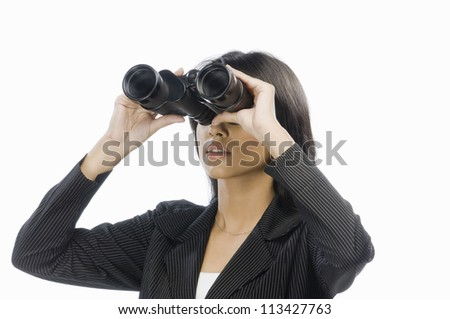 Businesswoman looking through binoculars - stock photo