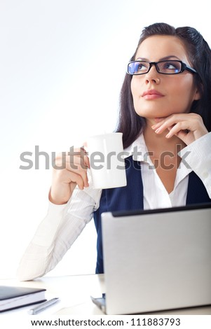 businesswoman looking up and holding cup of drink - stock photo