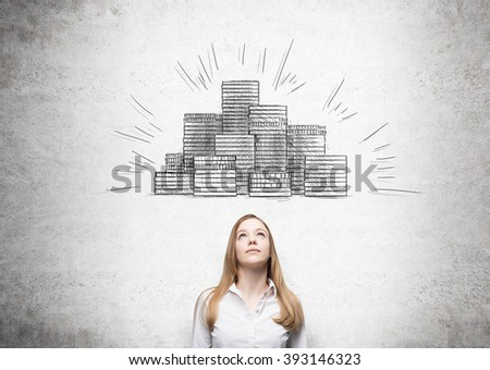 Businesswoman looking up, picture of coin piles drawn over her head. Concrete background. Concept of making money. - stock photo