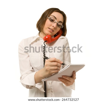 Businesswoman making a note while holding a handset - stock photo