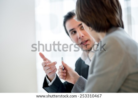 Businesswoman offering a pen to her business partner in order to close the deal with a signature. Focus on a pen. - stock photo
