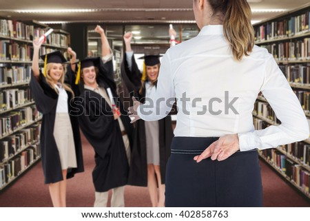 Businesswoman offering handshake with fingers crossed behind her back against entrance of the college library - stock photo