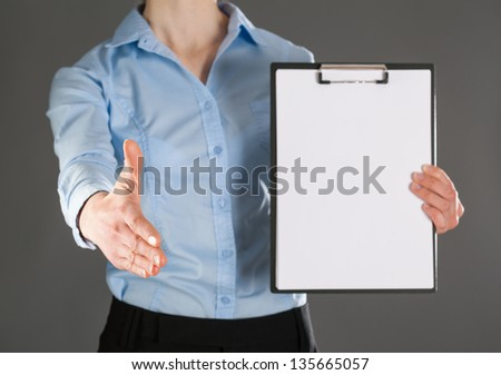 Businesswoman offers handshake to you and showing blank clipboard - stock photo