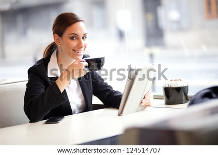 Businesswoman on a coffee break, using tablet computer - stock photo