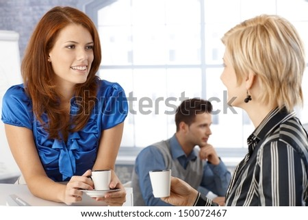 Businesswoman on coffee break, talking to colleague, smiling. - stock photo
