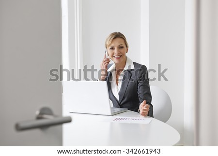 Businesswoman On Mobile Phone In Boardroom - stock photo