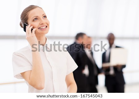 Businesswoman on the phone. Cheerful young woman in white shirt talking on the mobile phone and smiling while his colleagues standing on background - stock photo