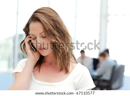 Businesswoman on the phone while her team is working in the background - stock photo