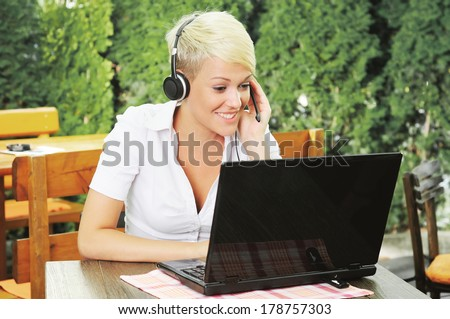 Businesswoman online talking via headset and looking at laptop - stock photo