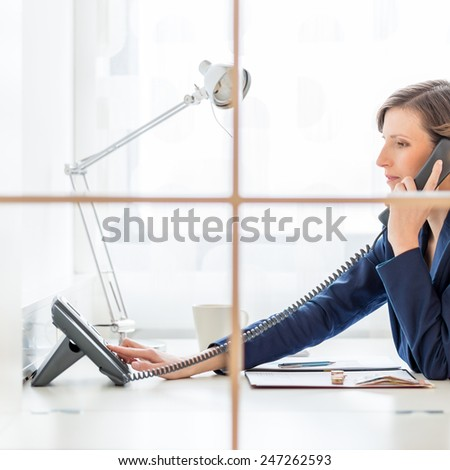 Businesswoman or personal assistant on a telephone call dialing out on a land line instrument as she sits at her desk, side view through an internal window. - stock photo