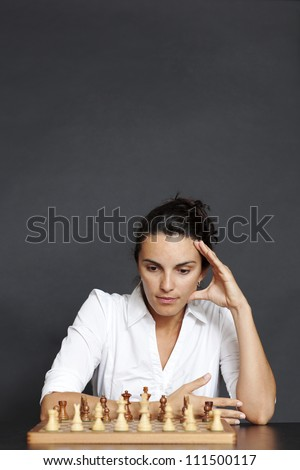 Businesswoman over a chess game - stock photo