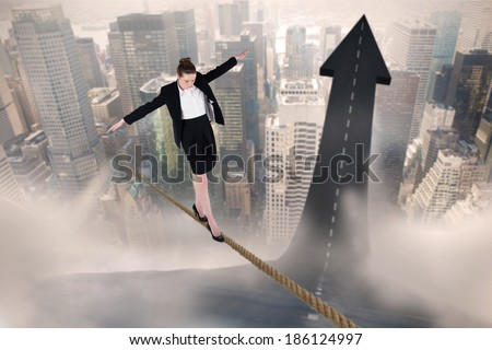 Businesswoman performing a balancing act against road turning into arrow - stock photo