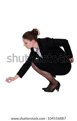 Businesswoman picking up a needle - stock photo