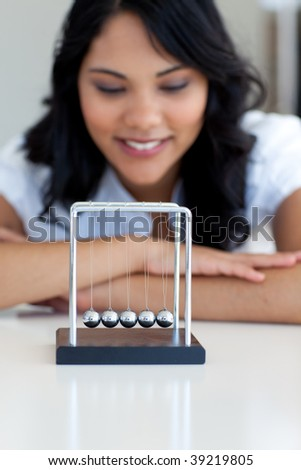 Businesswoman playing with kinetic balls in office - stock photo